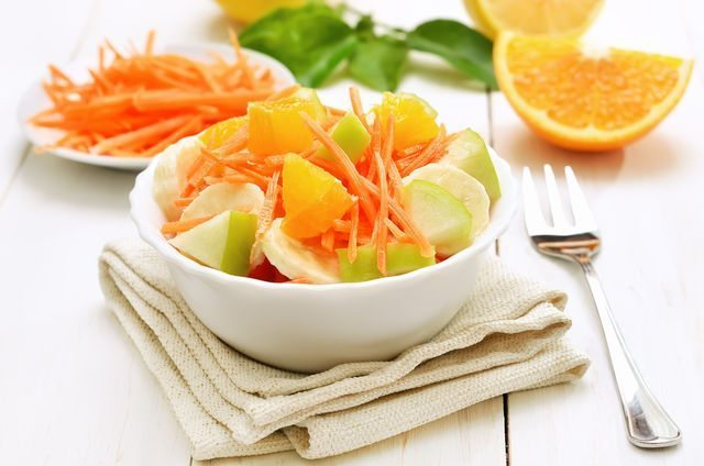 Fruit salad with carrots, apples, bananas and orange slices in bowl on white wooden table